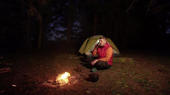 Thumbnail for Ein Mann trinkt Kaffee in der Nähe eines Lagerfeuers