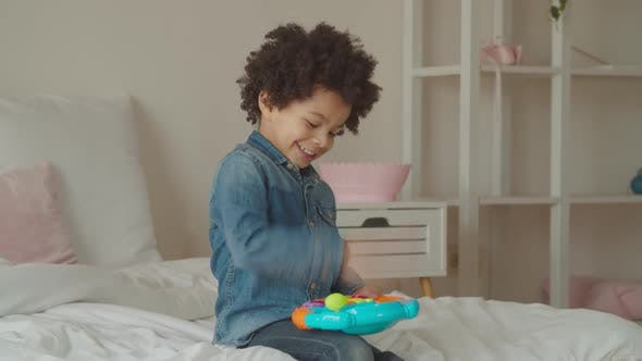 Cover Image for Joyful Kid Playing with Toy Steering Wheel Indoors