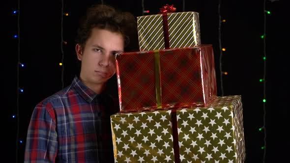 Thumbnail for Junge mit einer Geschenkbox auf schwarzem Hintergrund. Geschenkbox mit Band für Frohes Neues Jahr, Frohe Weihnachten