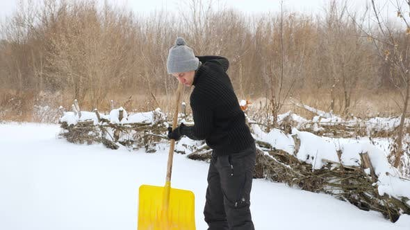 Young Man Cleans Snow with Yellow Plastic Shovel in Slow Motion