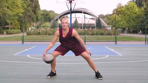 Aktive männliche Basketball-Spieler Üben Ball Handling Fähigkeiten durch Dribbling der Ball zwischen den Beinen