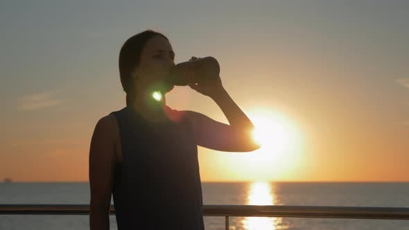Thumbnail for Young attractive smiling female athlete is drinking water at sunrise before run training.