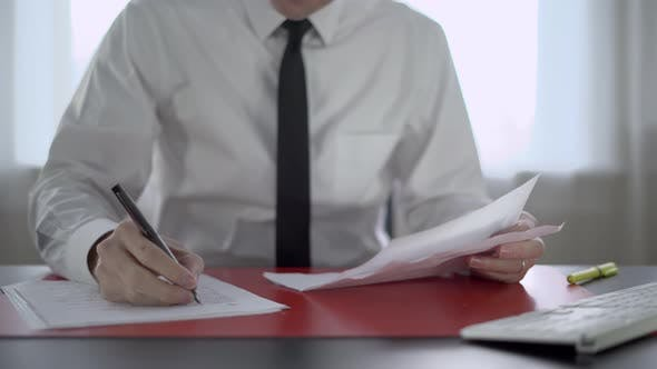 Cover Image for Man Going Through Paperwork at His Desk