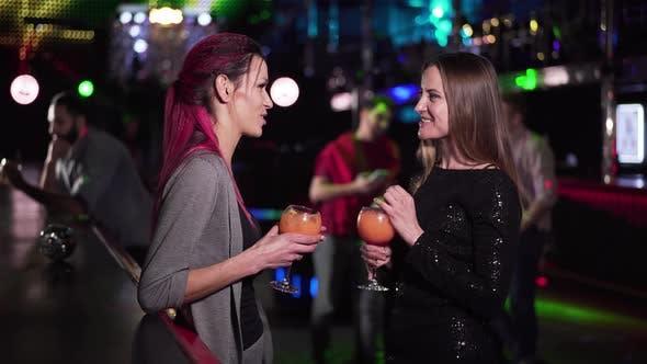 Thumbnail for Zwei positive kaukasische Mädchen stehen mit Cocktails an der Bar Theke, sprechen und winken zu Männern