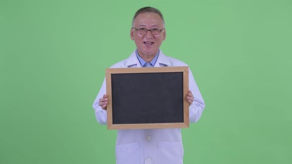 Thumbnail for Happy Mature Japanese Man Doctor Talking While Holding Blackboard