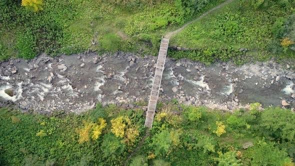Thumbnail for Aerial view of wood bridge crossing transparent river.