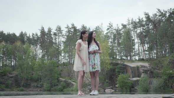 Thumbnail for Two Beautiful Women Standing, Talking, Smiling. Girls Looking at Amazing Nature