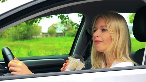 Thumbnail for Young Attractive Blond Woman Sits in the Car and Drinks Ice Coffee in Cup