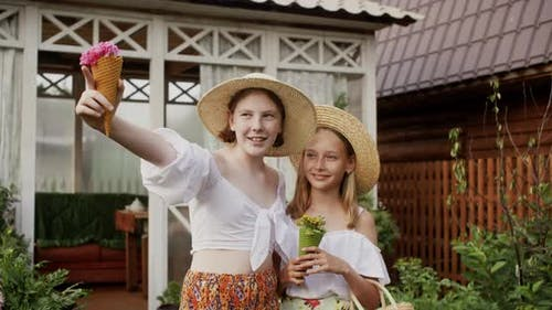 Rural Teenager Girls in Straw Hat in Countryside with Wildflowers on Wooden House Background Showing