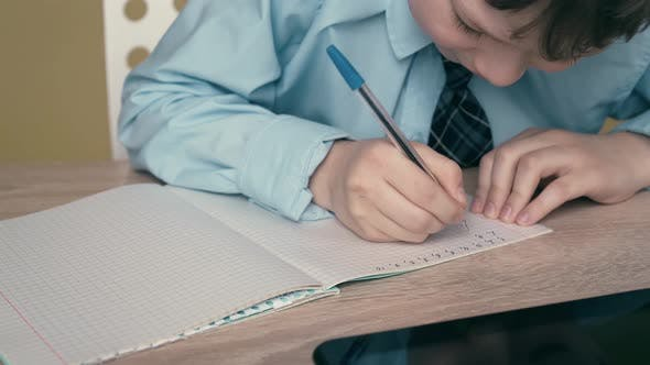 Thumbnail for Ext CU, Tracking: Schoolboy Does Homework, Writes a Pen in a Notebook, on the Table Is a Tablet.