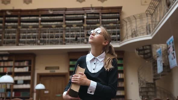 Thumbnail for Blond Teen Girl in Glasses Which Holding Thick Book and Coming Through the Library Room