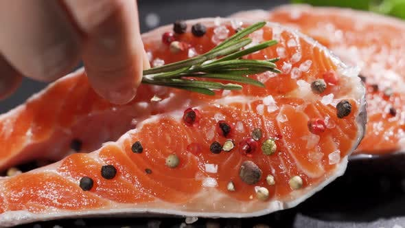 A Cook Puts a Sprig of Rosemary on a Salmon steak.Raw Salmon Red Fish with Pepper and Salt
