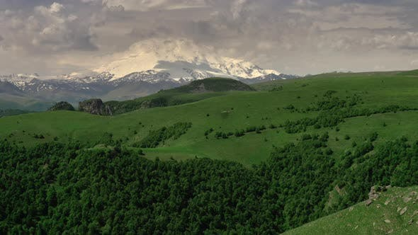 Mount Elbrus and green hills at sunny summer day.