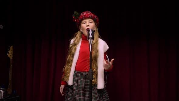 Junges Mädchen in Weihnachten Konzept singt Song Front Retro Mikrofon auf der dunklen Bühne