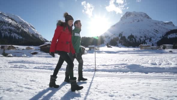 Thumbnail for A man and woman couple walking in the snow at a ski resort in the snow at the mountains.