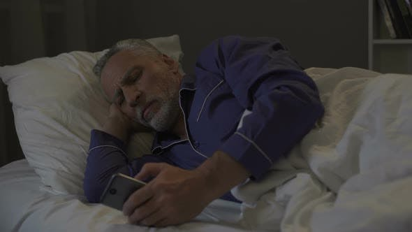 Thumbnail for Addicted to smartphone senior man scrolling application instead of sleeping