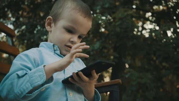 Thumbnail for Little Boy Playing Video Games on His Smartphone Outdoors.