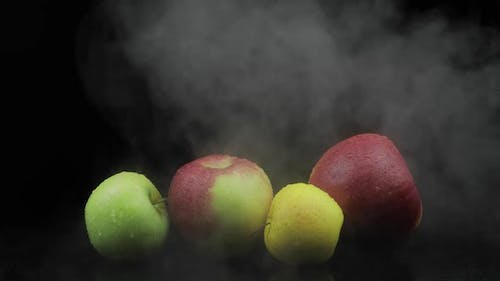 Tropical Fruit Apple in Cold Ice Clouds of Fog Smoke on Black Background