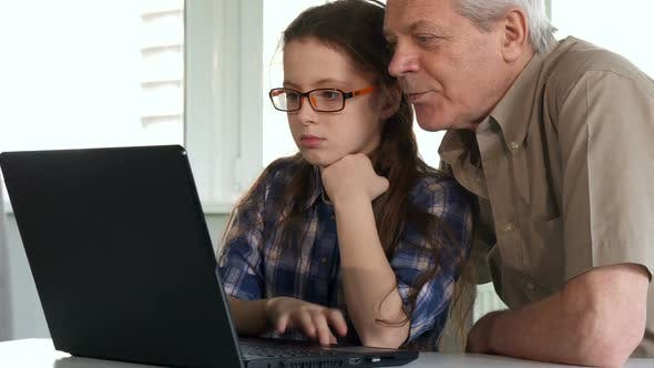 Thumbnail for Senior Man and His Granddaughter Watch Something on Laptop