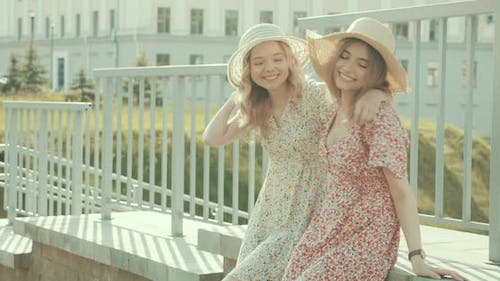 Two young beautiful smiling hipster girls in trendy summer sundress posing outdoors