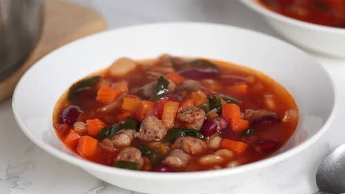 Beans tomato soup with sausages in white plate.