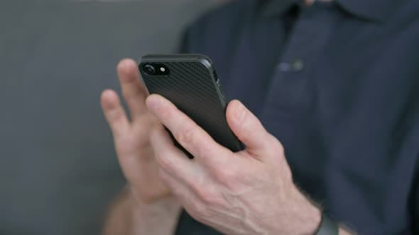Cover Image for Close Up of Hands of Man Using Smartphone