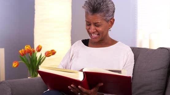 Thumbnail for Mature Black woman looking through photo album