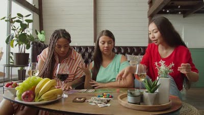 Diverse Female Friends Playing Board Game Sitting on Floor Indoors