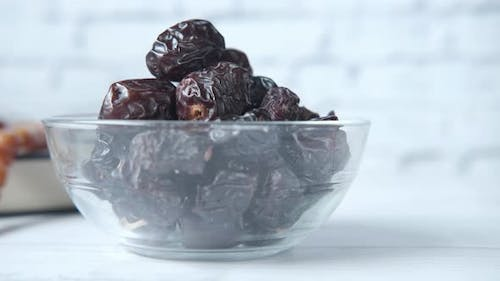 Close Up of Fresh Date Fruit in a Bowl and Quran on Table
