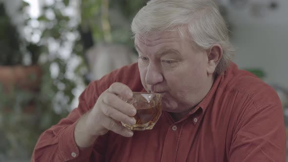 Cover Image for Close-up Portrait of Senior Man Drinking Whiskey Sitting at Home. The Elderly Man with a Glass of