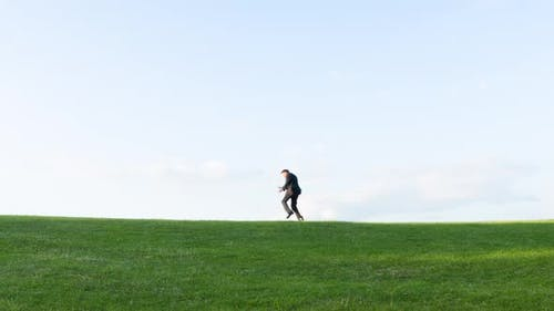Crazy businessman dancing on a hill
