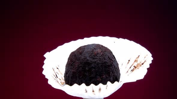 Handmade Black Chocolate Candy in White Paper Rotates