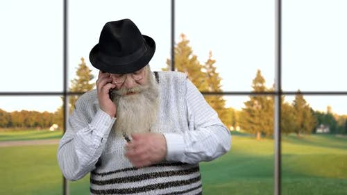 Old Bearded Man Talking on Cell Phone.