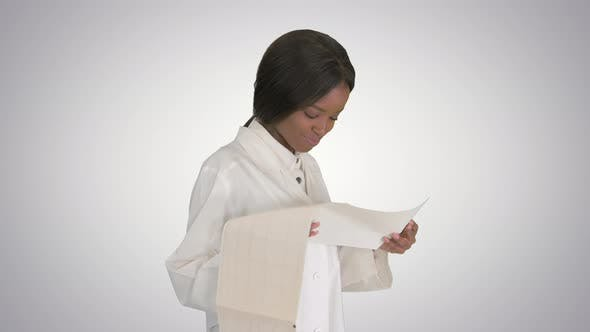Thumbnail for Smiling African American Female Doctor Reading Cardiogram on Gradient Background.
