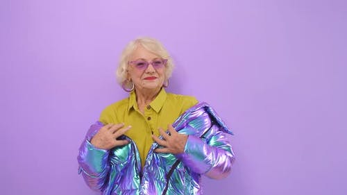 Modern Elderly Woman with a Smile Enjoys Her Age Posing for the Camera on an Isolated Background