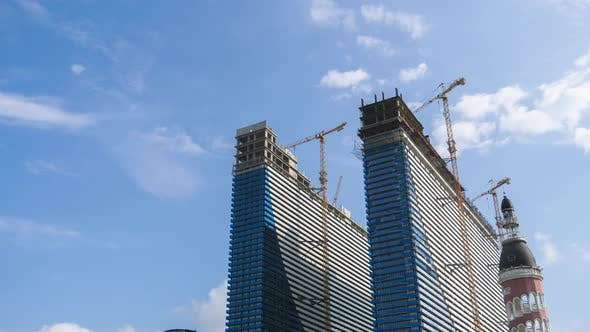 Construction of a Modern Skyscrapers Using Tower Cranes, Timelapse, Moving Clouds on Blue Sky