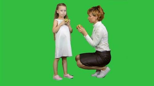 Glückliche Mutter mit Tochter essen gesundes Essen auf einem Grün
