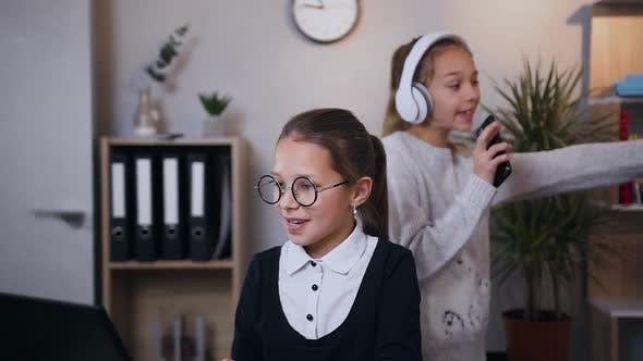Thumbnail for Schoolgirl in Glasses Showing Something Interesting to Her Older Sister that Dancing