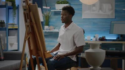 African American Person Sitting in Art Studio with Drawings