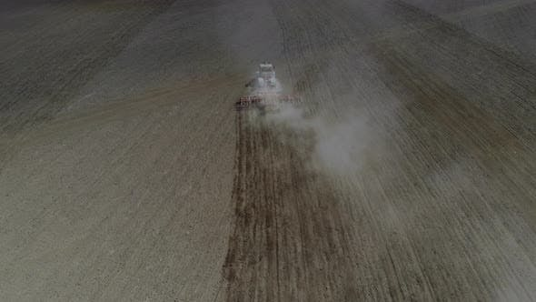 A Tractor Cultivates the Soil in the Field.