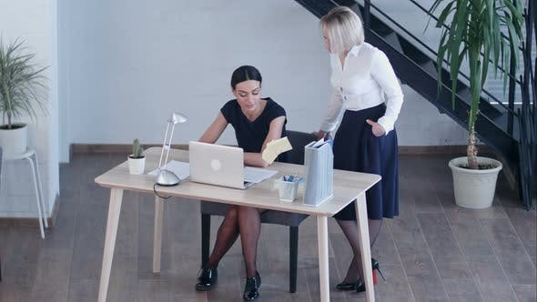 Thumbnail for Two Women Working Together with Documents and Laptop at Office