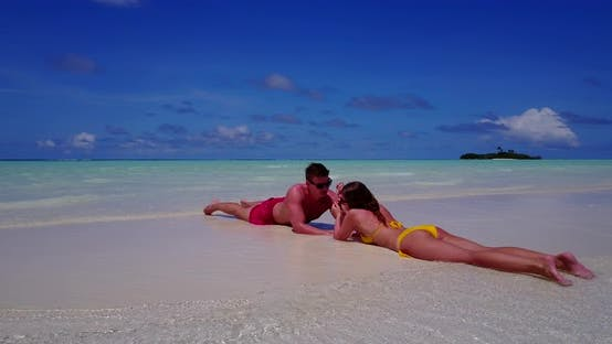 Beautiful boy and girl in love dating on vacation live the dream on beach on clean white sand