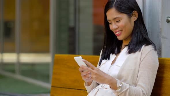 Thumbnail for Asiatische Frau mit Smartphone sitzen auf Bank