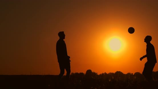 Thumbnail for Two Boys Playing Soccer at Sunset. Silhouette of Children Playing with a Ball at Sunset. The Concept