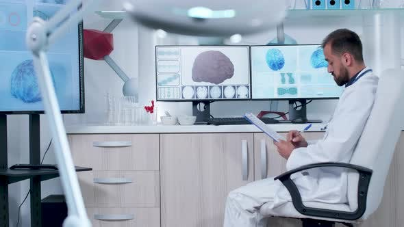 Doctor Taking Notes About 3D Brain Scan and Animated DNA Strings