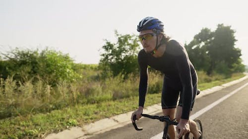 Professional Cycling Athlete Riding Racing Bicycle Training for Competition Race on Open Road