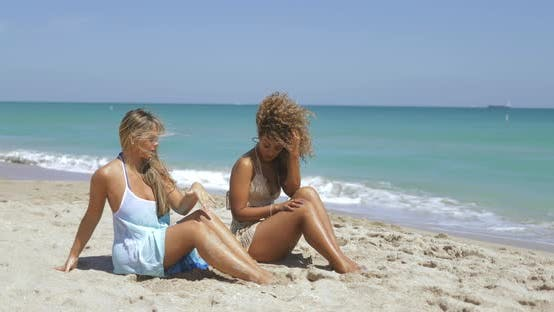 Laughing Diverse Women Chilling on Beach
