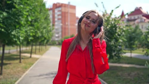 Beautiful young woman with headphones. Happy girl walking and enjoying listening to music