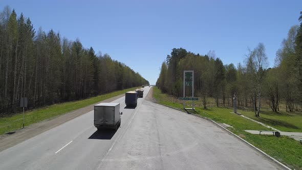 Entrance to the city. Cars drive along the highway.