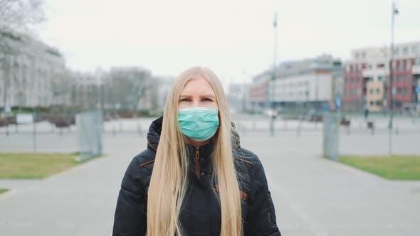 Thumbnail for Coronavirus Pandemic: Blonde Woman in a Medical Mask Walking Down the Street